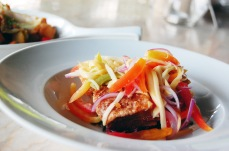 Binagoongan: Crackling pork belly on grilled eggplant and shrimp paste, crowned with a generous foliage of green mango, tomato, and onion